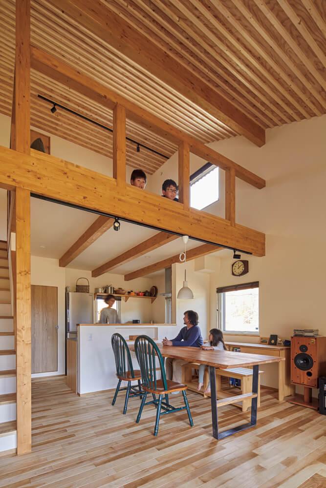 天井なりの高い吹き抜けが心地よいダイニング。大きなサクラ材のテーブルは、近所の木工作家が仕上げた天板に、芦野組が脚を造作して完成させた。ダイニング壁側には可動式造作学習机が並ぶ。将来は子ども部屋に移動する予定