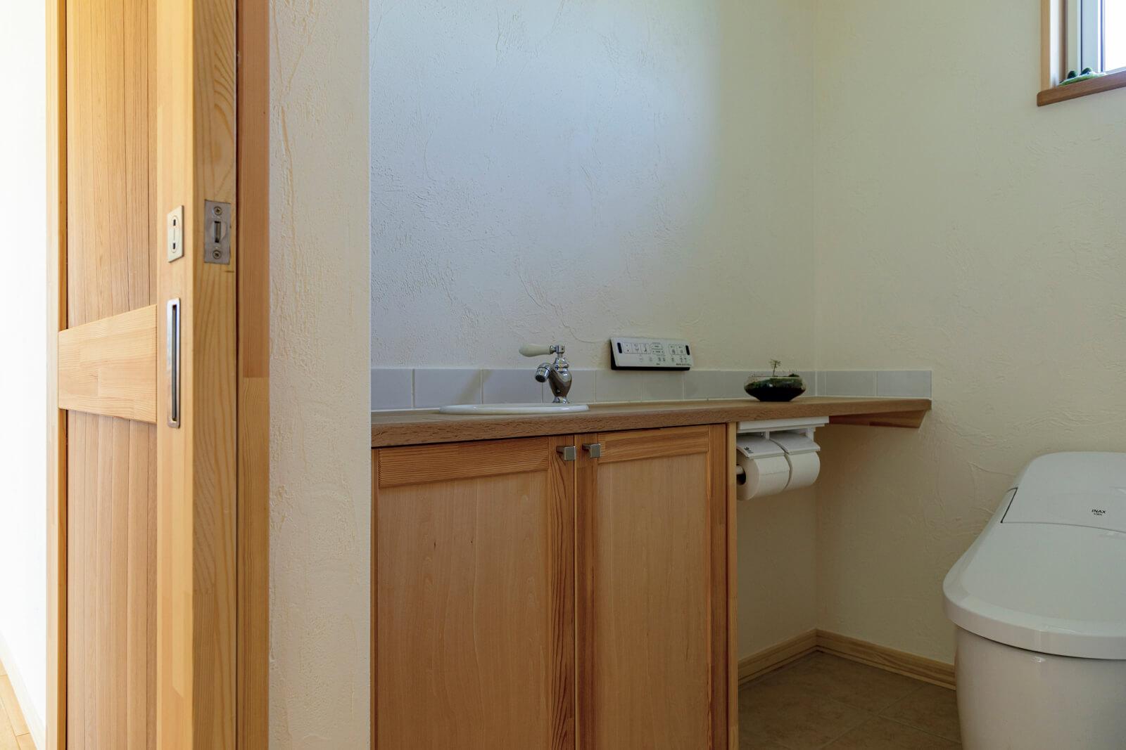 トイレにも木を生かした手洗いや収納を造作。配慮の行き届いた気持ちいい空間になっている