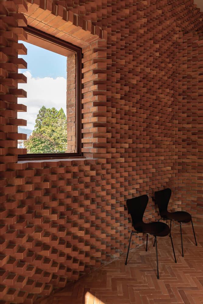北海道江別産の煉瓦で規則正しく積み上げられたエントランスの壁面。壁のジグザグ模様がそのままヘリンボーン柄の床へとつながるような独特なデザインだ