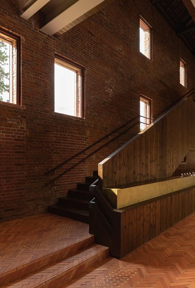 窓からの光が心地よい陰影をもたらす階段まわりの空間。階段左手の壁は、漆喰をはがして既存の煉瓦壁を現しにした。パイン材で仕上げたカウンターの腰壁と、手すりとの一体感を持たせた手すり壁が1階と2階の連続性を表現。シードル・ゴールドに塗装したステンレスのカウンターとの組み合わせも美しい