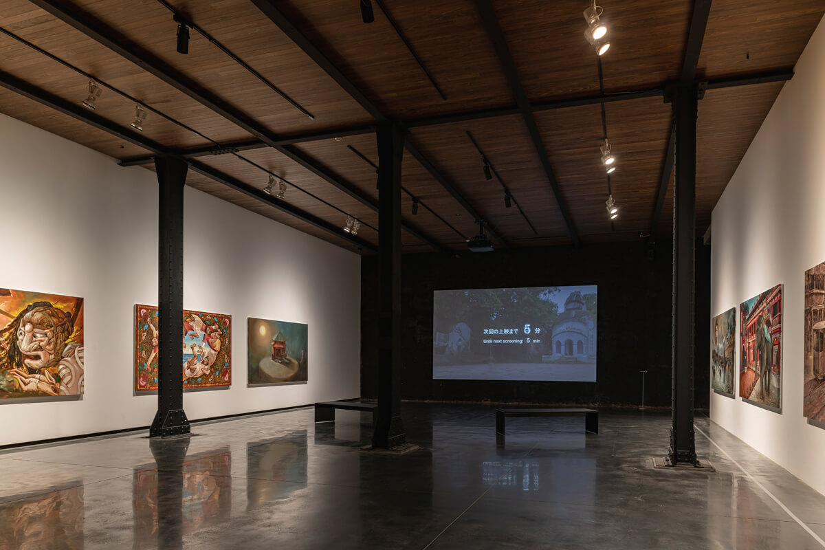 既存の建物のリベット(鋲)溶接が打ち込まれた鉄柱に支えられた1階の展示室。コールタールの黒い壁を部分的に活かすなど、この建物ならではの展示空間となっている (「小沢剛展 オールリターン ー百年たったら帰っておいで 百年たてばその意味わかる」展示風景)