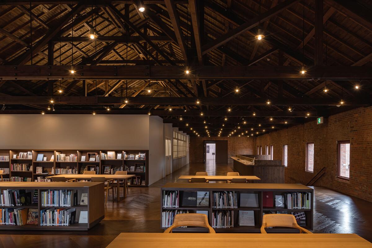 2階にある美術関係の出版物などを閲覧できるライブラリー。白い壁に囲まれたエリアは美術館の事務所として使われている。天井一面に広がる木造の小屋組みは、古いものと新しいものが調和するように配慮しながら、部分的な梁の入れ替えや構造補強などの改修工事を行った