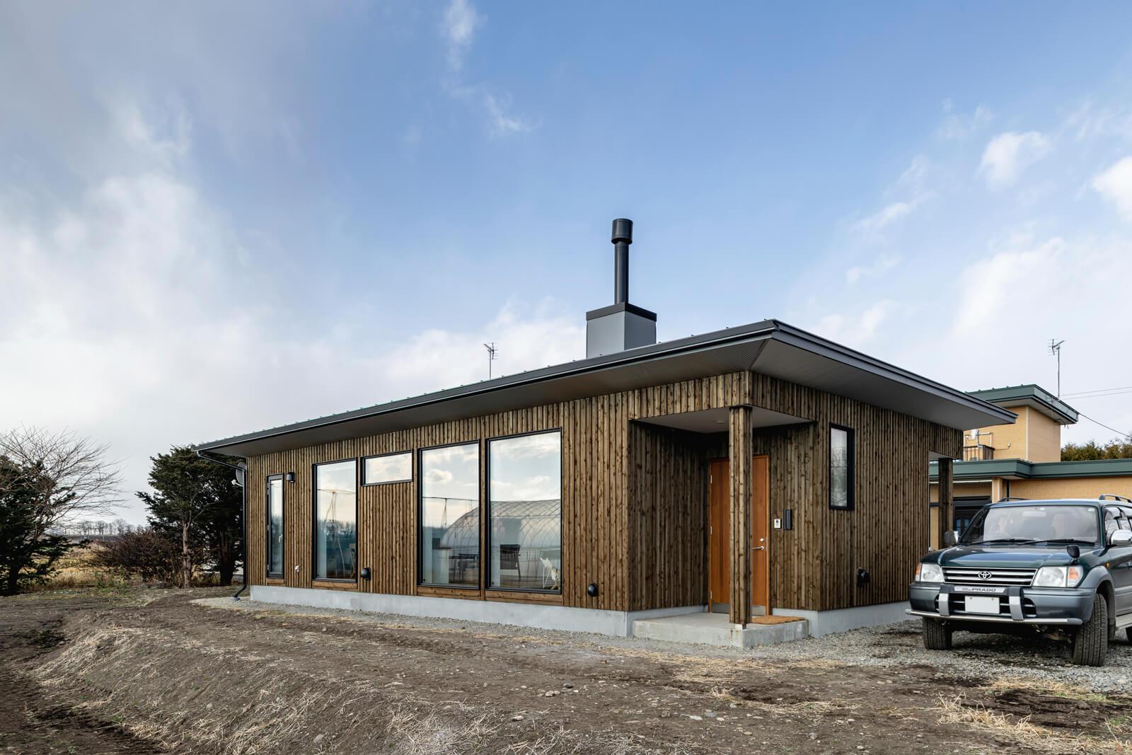 畑のほとりに建つカラマツ板張りの平屋。薪ストーブの煙突と大開口が、直線的なフォルムのアクセントになっている