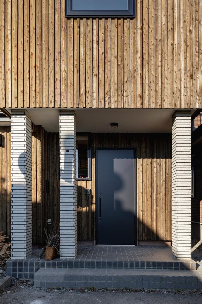 玄関ポーチのタイル張りの柱は、既存のものを再利用。タイルとカラマツのコントラストが外観のアクセントになった
