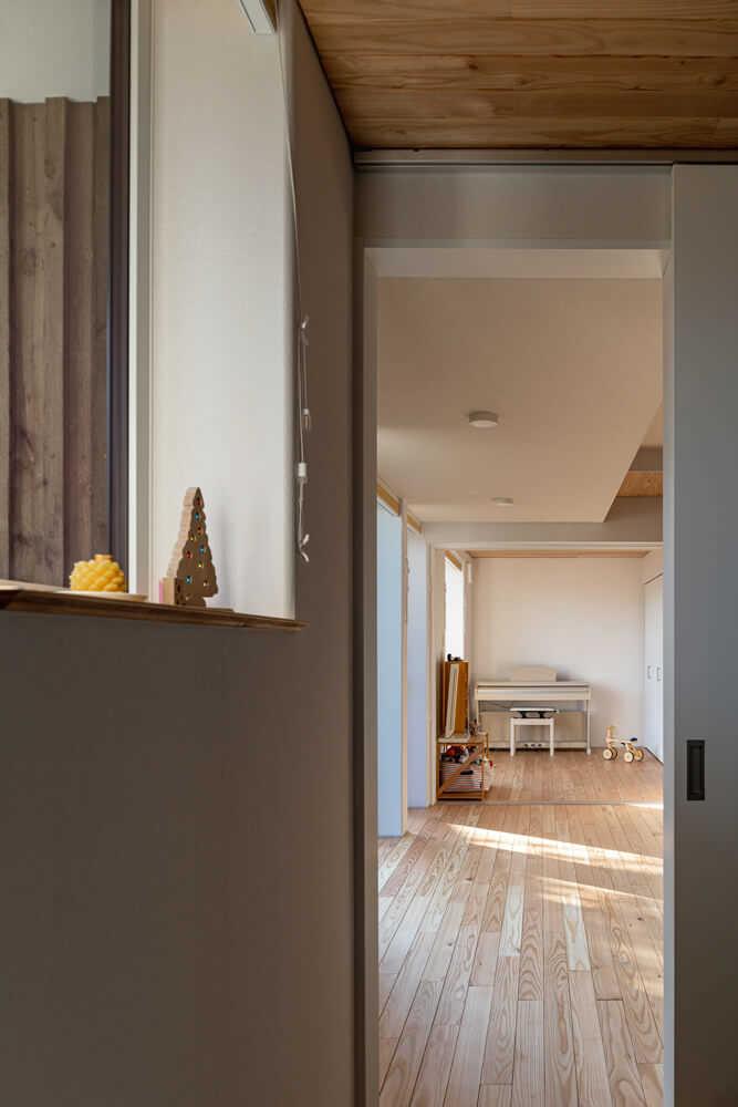 大きな採光窓を用いた明るい玄関ホールは、そのままリビングにつながる。突き当たりは子どものプレイルームとして重宝している予備室