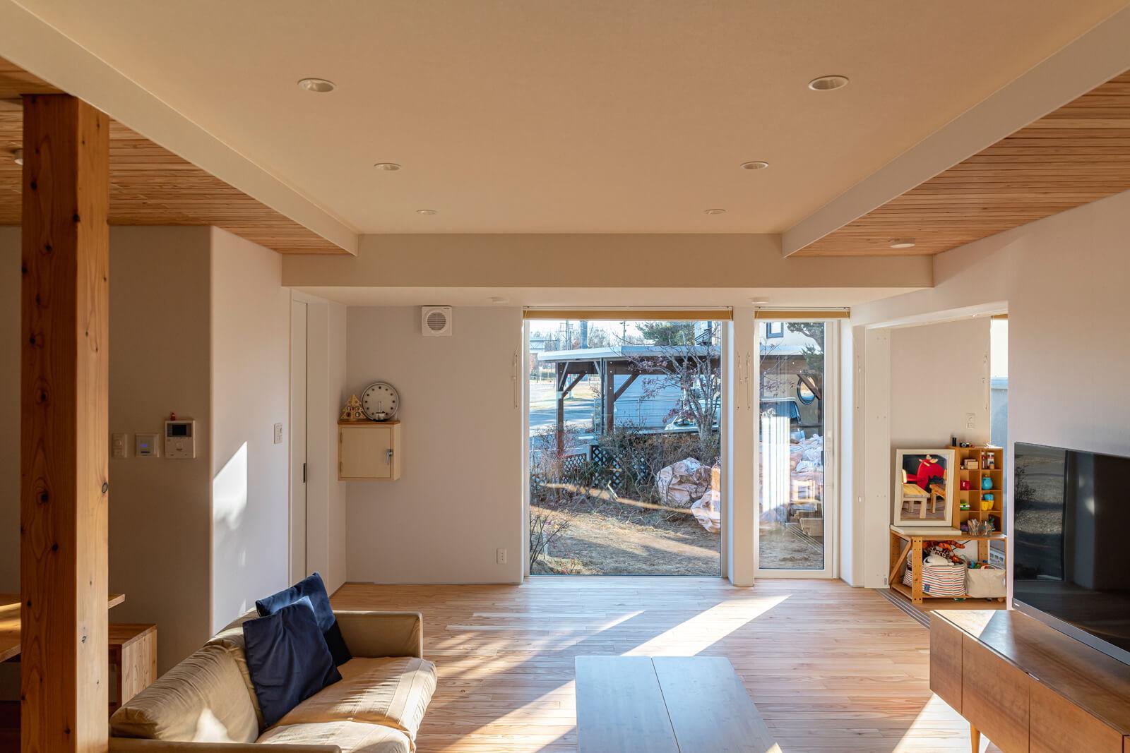 大開口からたっぷりと陽射しが入るリビングは、天気のいい日は暖房いらずの暖かさ。外光が美しい陰影を描く壁には、木製チップ入りのオーガニッククロスを採用