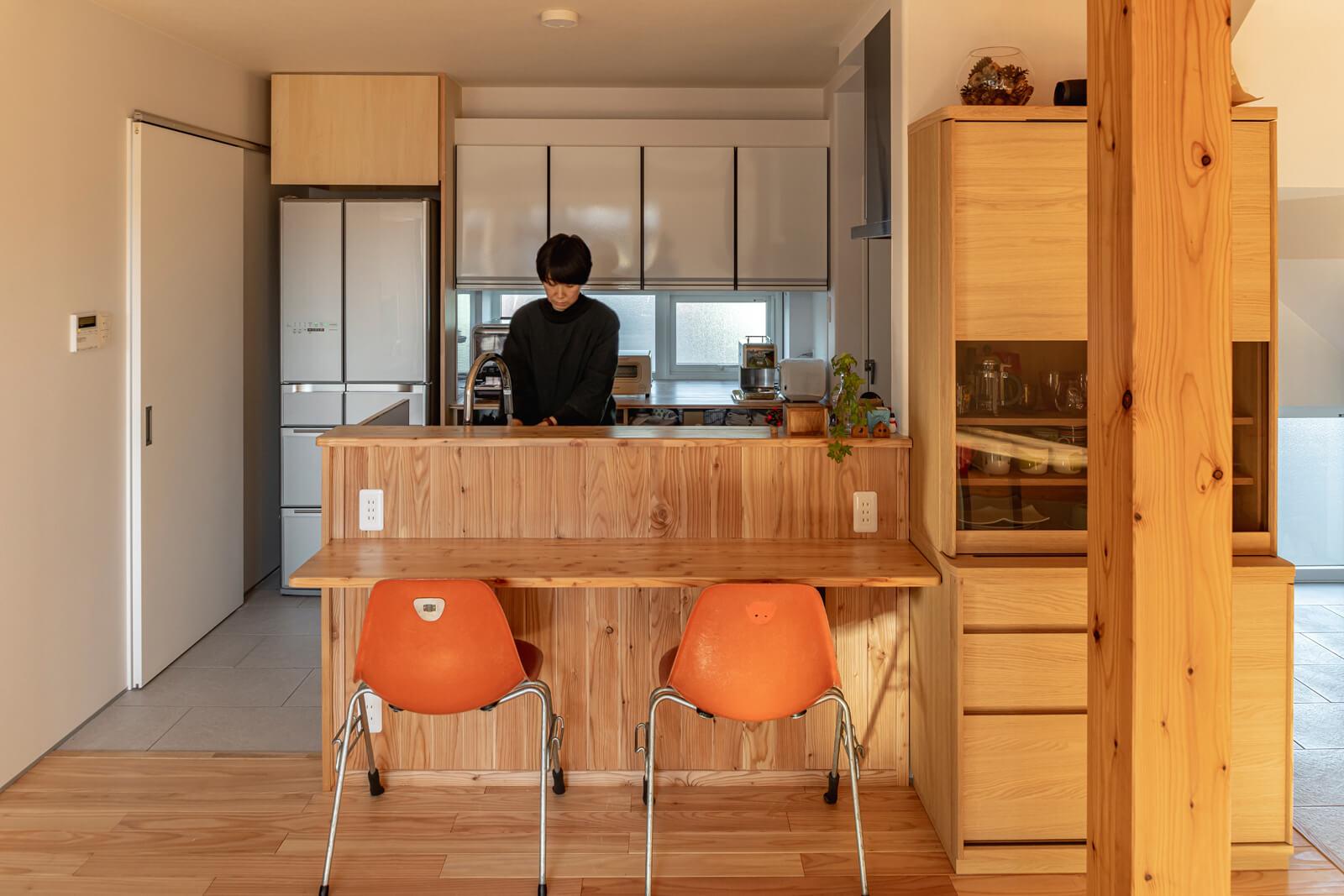 リビング・ダイニングを見渡す対面式キッチン。リビング側には造作カウンター付きの腰壁を設けた。白い引き戸を開けると、ランドリーを兼ねた脱衣室がある