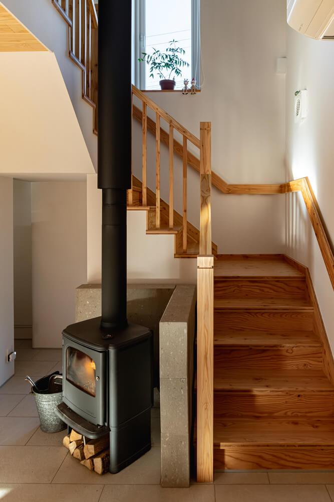 水野建設に依頼して選んでもらった薪ストーブはモルソー製。防火壁として、札幌軟石を背面に積んだ。ストーブまわりからキッチン、水まわりまで、床はタイルで仕上げた