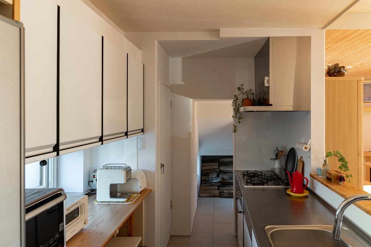 キッチンから動線がつながる階段下スペースには薪保管庫が設けられている。薪を外から保管庫へ直接運び込める鍵付きの開口も備える
