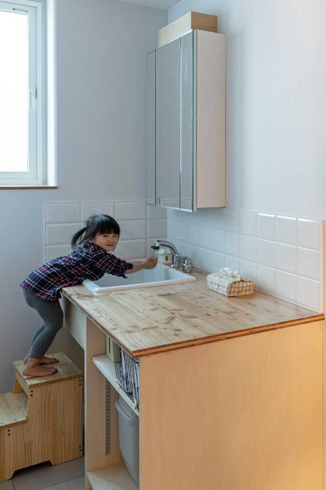 奥さんの希望で脱衣室から分離した洗面室には、造作仕様の洗面台を設置。小さな子どもが使いやすいよう、踏み台も造作