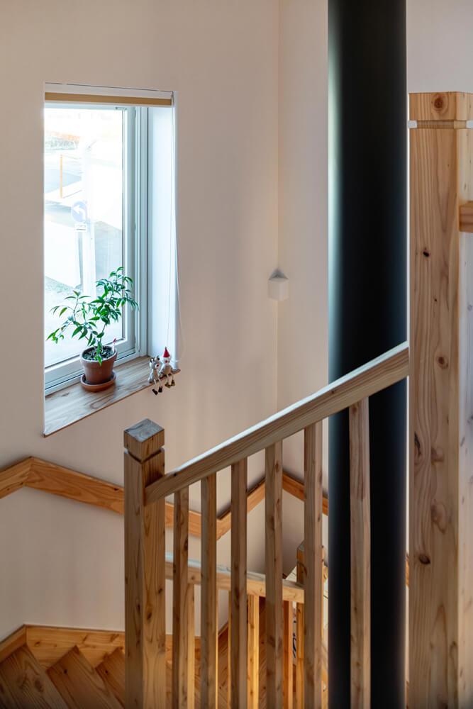 階段吹き抜けを貫く薪ストーブの煙突が、2階へも薪火の暖かさを伝える。採光窓から入る外光が、階段を明るく照らす