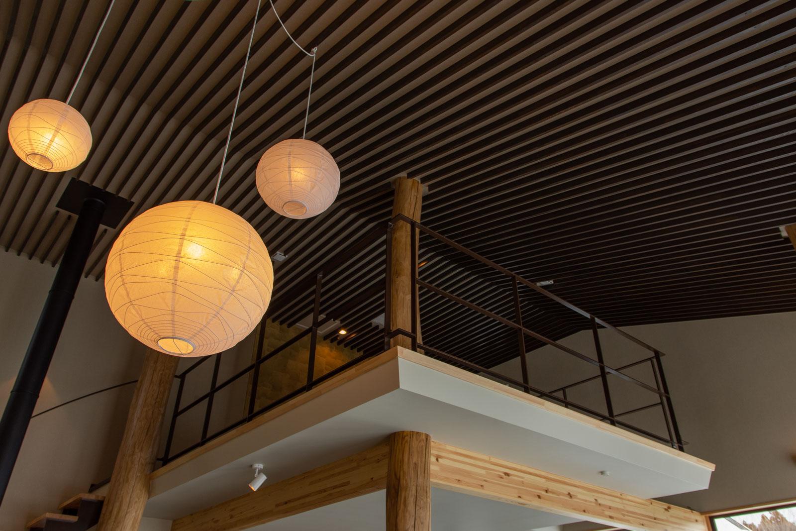 リビングから吹き抜けを見上げる。2階は屋内テラス風の空間にし、吹き抜けとの空間的つながりを優先した