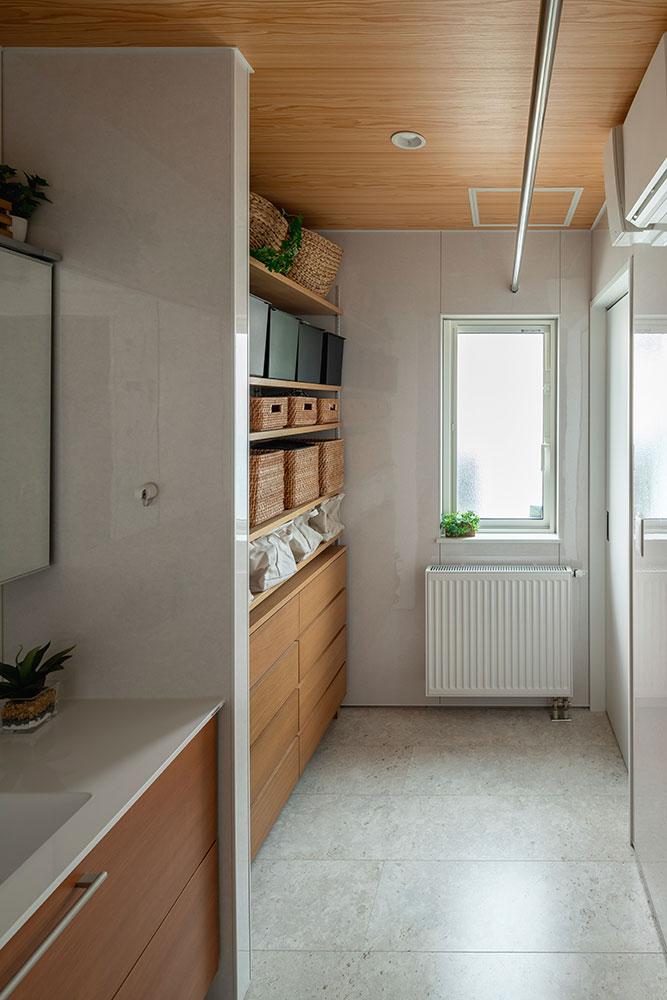 奥に長い洗面+ランドリースペース。洗面台の並びには大容量の収納棚があり、タオルや下着類などを収納しておくことができる