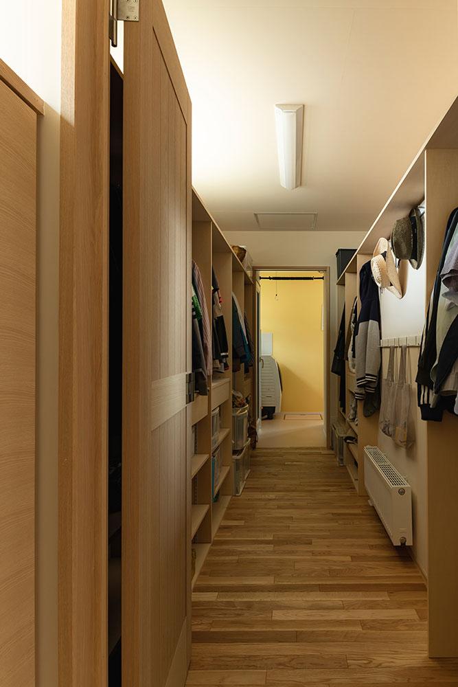 玄関ホールから両サイドに収納棚を造りつけたファミリークローゼットへ。その先にランドリールーム