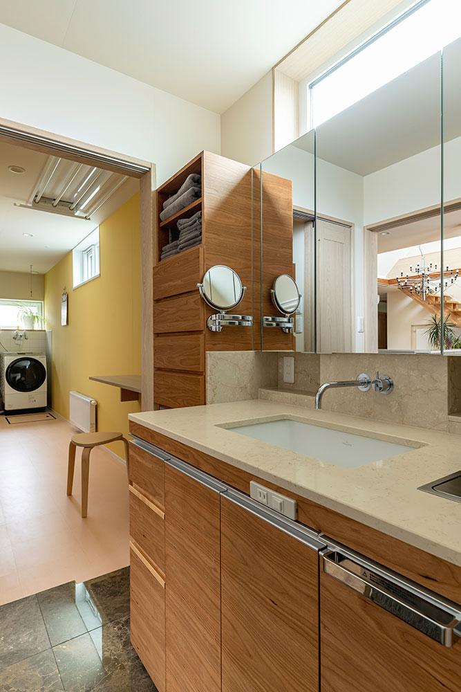 ランドリールームと洗面脱衣室は隣り合っていて、引き戸で仕切れる設計。洗面脱衣室・浴室をキッチンとつなげて回遊動線をつくっている