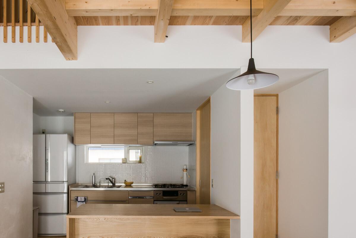 ダイニングテーブルはフローリングと同じ素材で製作し、白タイルの壁と既製品のキッチンをうまく合わせたデザインに
