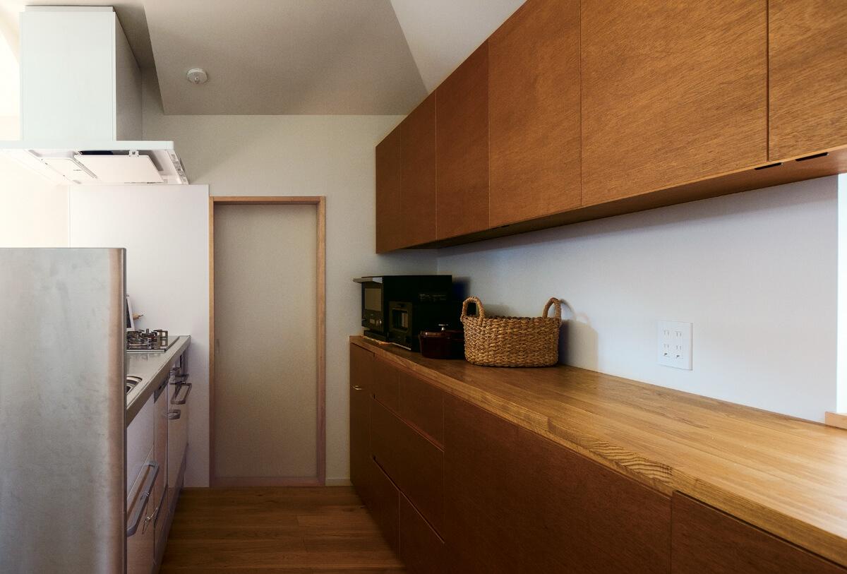 キッチンはシンクとコンロの対面に造作棚を設けて収納問題を解決。奥の扉はパントリーに通じる