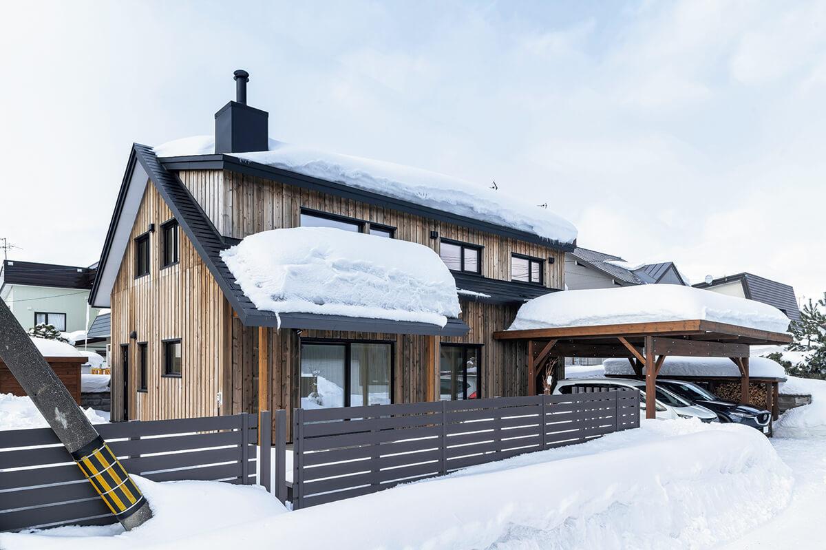 三角屋根と煙突、道南スギの外壁が温かな印象を与える外観。カラマツのカーポートを玄関前に配し、冬の雪対策も万全