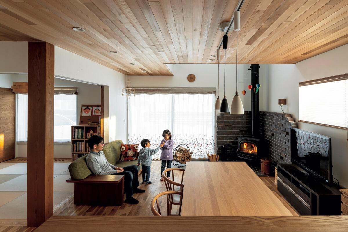 レッドシダーの天井とナラ無垢床、塗り壁、薪の炎が美しい調和を見せるLDKは、Yさん一家お気に入りのくつろぎ空間