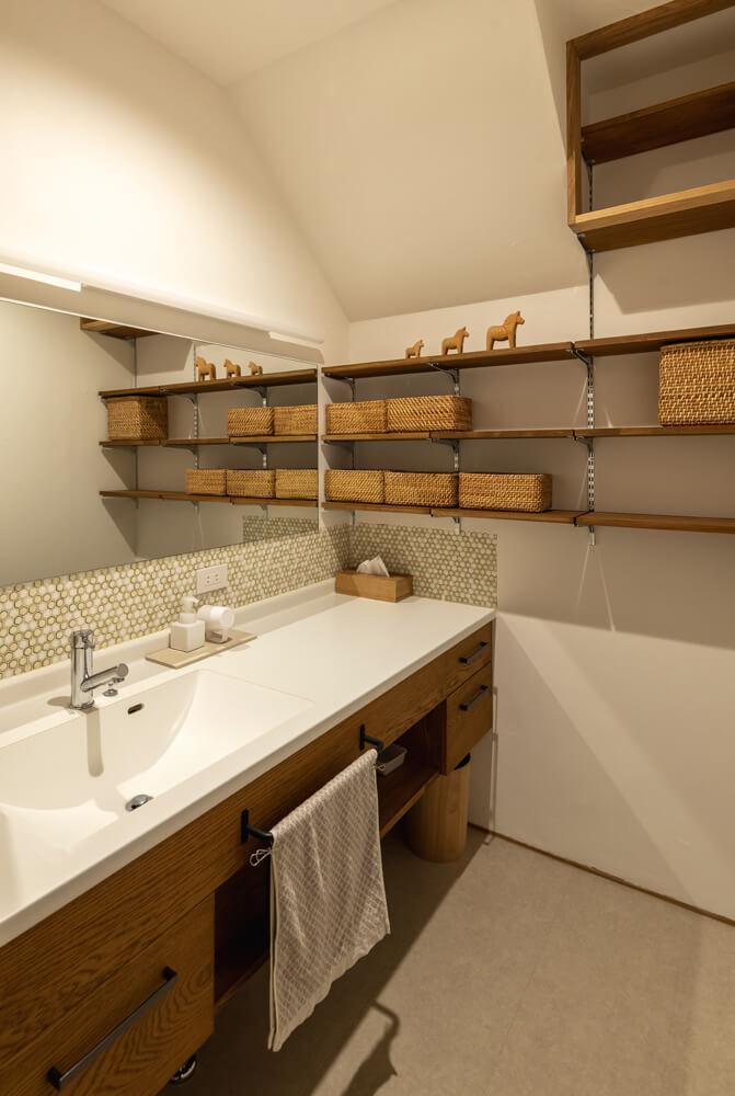 ユーティリティと分離した独立型の洗面スペース。タイル使いや収納棚など奥さんの要望を造作で叶えた