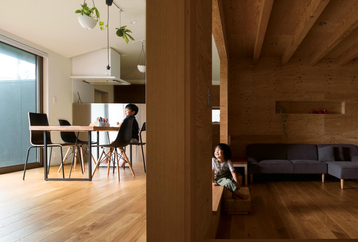 リビングとダイニングは床レベルの違いのほか、内装の仕上げも変えることで空間にリズムを生んでいる