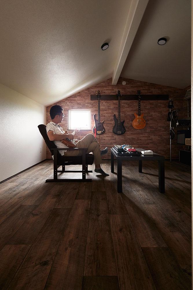 レンガ風のアクセントウォールに趣味のギターを飾ったこもり空間は、すっかり居心地の良いご主人の城に