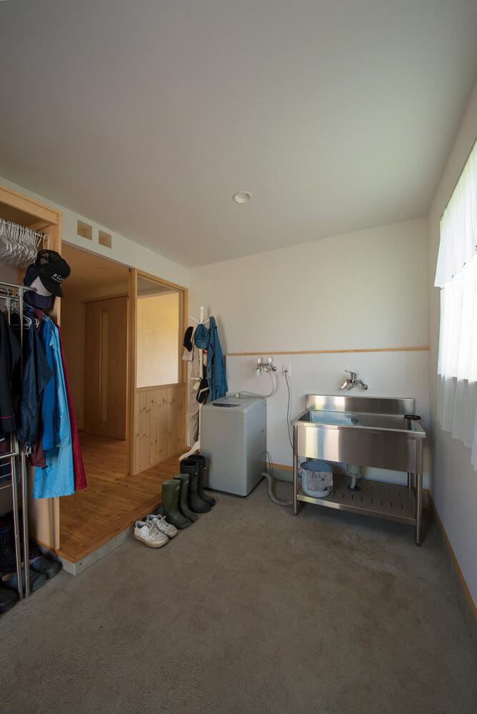 作業や着替え、洗濯もできるよう広く取った裏玄関の土間が便利