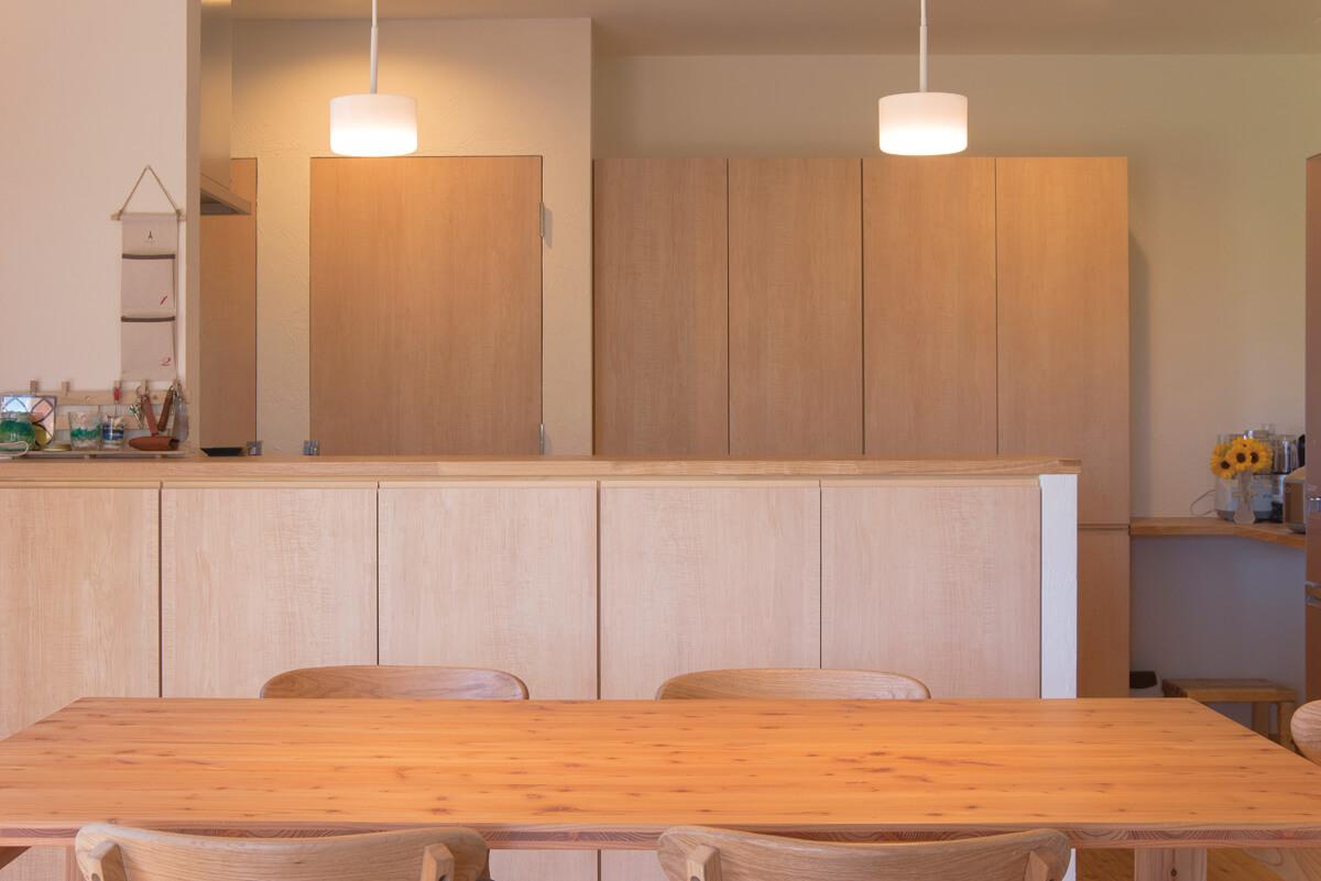 収納スペースもたっぷりのキッチン。ダイニングテーブルも合わせて造作した