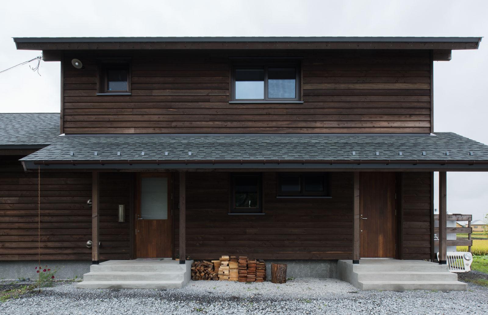 道産カラマツを張った外壁と長い庇が印象的な外観。右側が事務室や水まわりなどへ最短の動線で出入りできる裏玄関