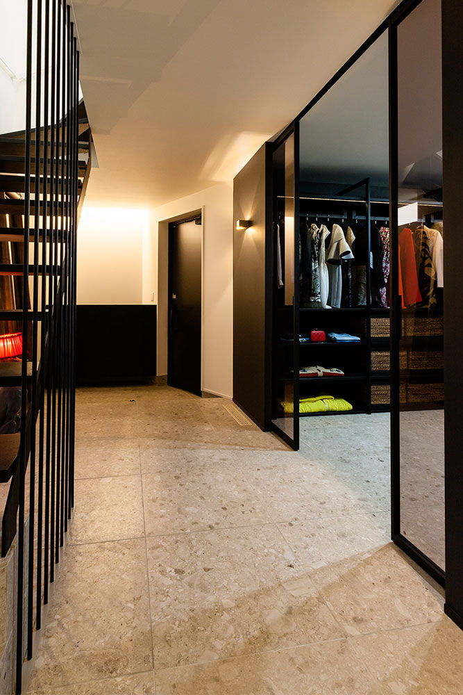 アイボリーの石調タイルと、建具や階段のブラックのコントラストが高級感を醸す