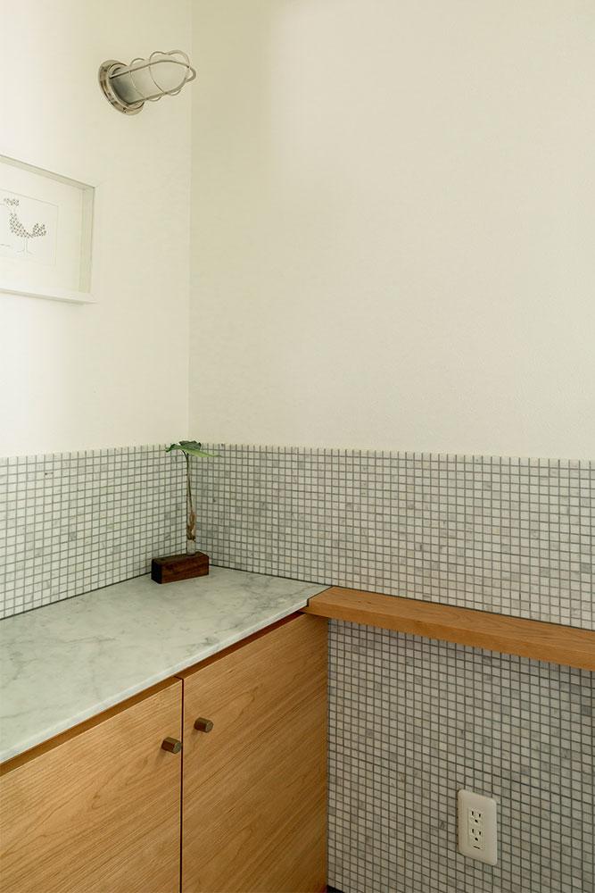 石のような風合いのモザイクタイルで仕上げたトイレの腰壁