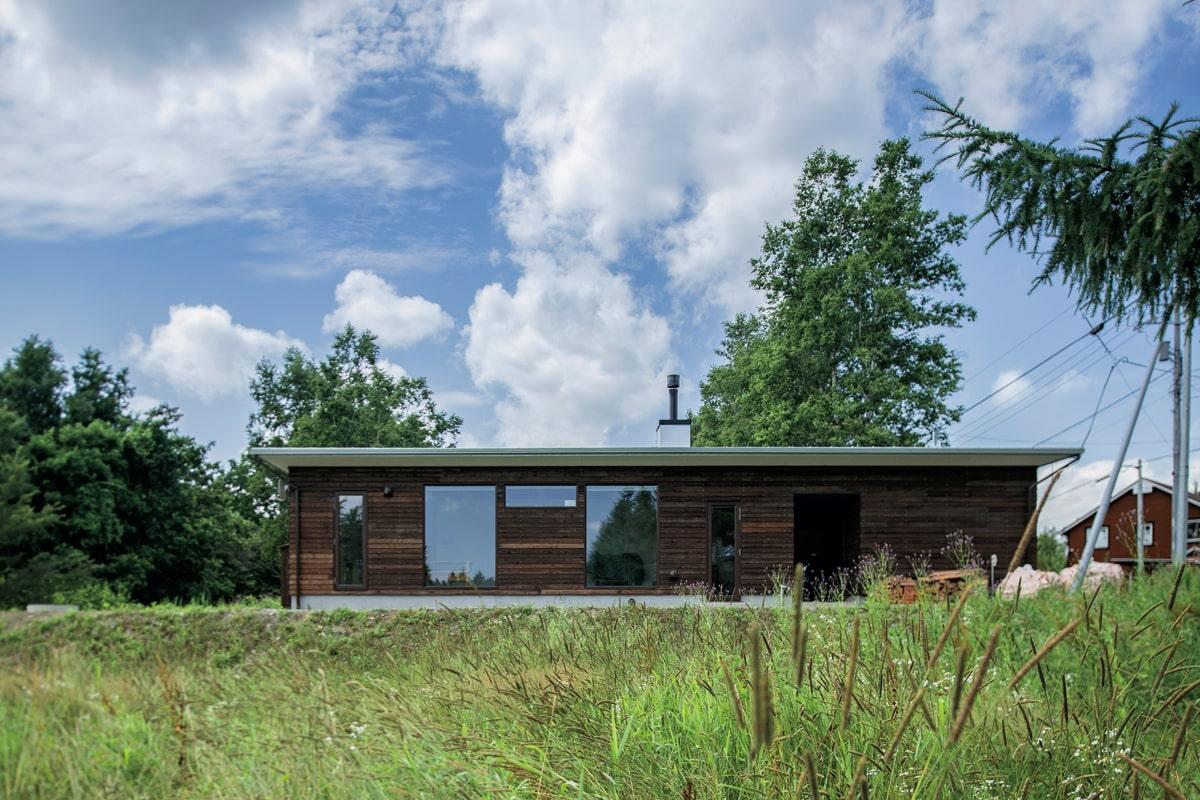 直線的なフォルムが印象的なカラマツ横張りの外観。無公害木材保護保持剤「ウッドロングエコ」を塗装している