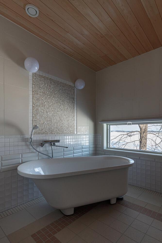 「湯船につかりながら、木々の緑や星空を眺めたい」という、奥さんの要望で実現した造作バスルーム。繊細なタイル使いもとかち工房ならでは