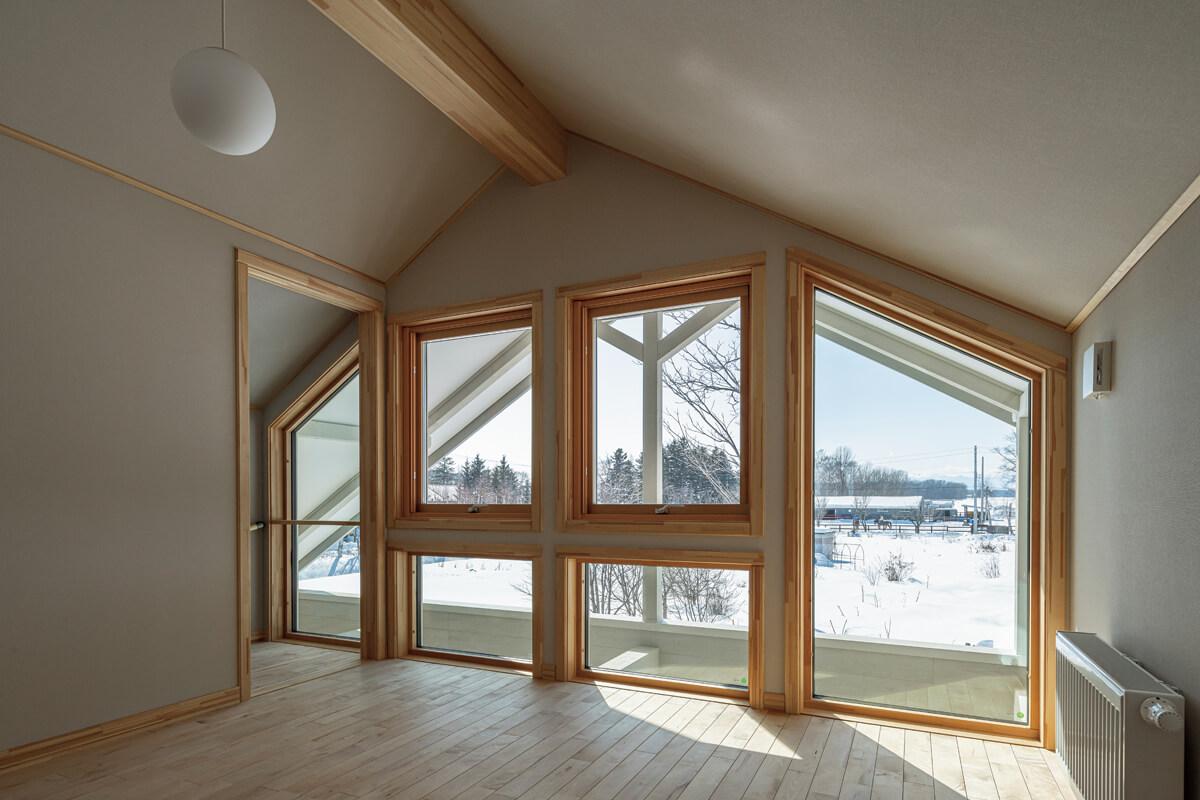 木製サッシの大開口が設けられた2階階段ホールは明るく、開放的な雰囲気。ファサードのアクセントにもなっている