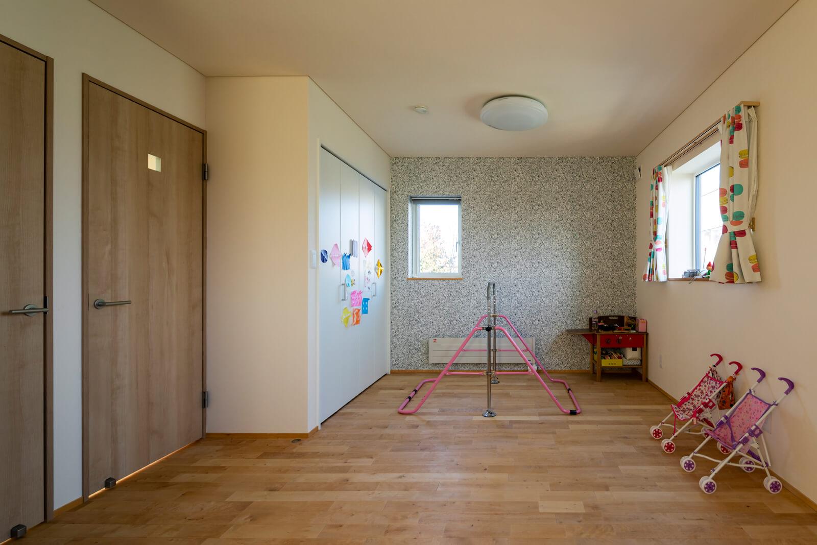 将来的に仕切ることができる仕様の子ども部屋。ポップなカーテンやアクセントクロスがかわいらしさを演出