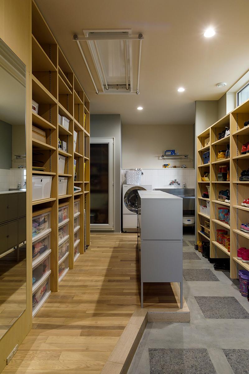 広い土間玄関は公私を振り分ける大切な場所。写真奥は洗濯機や手洗い場が設けられた仕事用動線、手前はプライベート用動線となっている。「子どもたちのランドセルや着替えも集約し、すべてここで完結できるようにしています」と奥さん