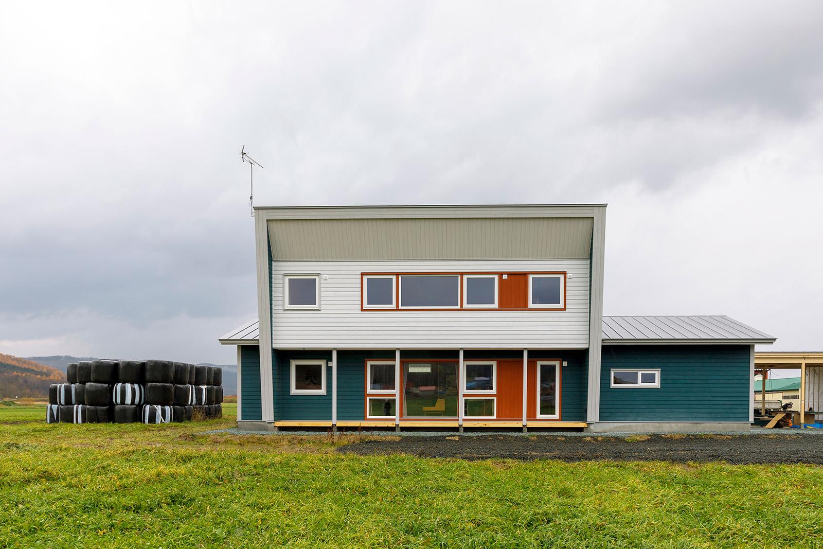 牧草地の中に建つAさん宅の外観は、片流れと三角屋根の組み合わせというAさんの希望が叶えられたもの。「自然界の中にある色を使い、周辺環境と調和するように、という澤田さんのアドバイスのもと、緑と土を意識したカラーをセレクトしました」