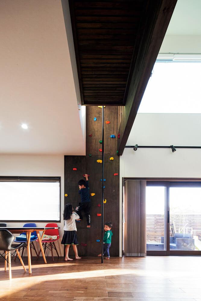 リビングに据えられたボルダリングの壁とのぼり棒。上り切った先は2階ホールにつながっていて、回遊しながら遊べる
