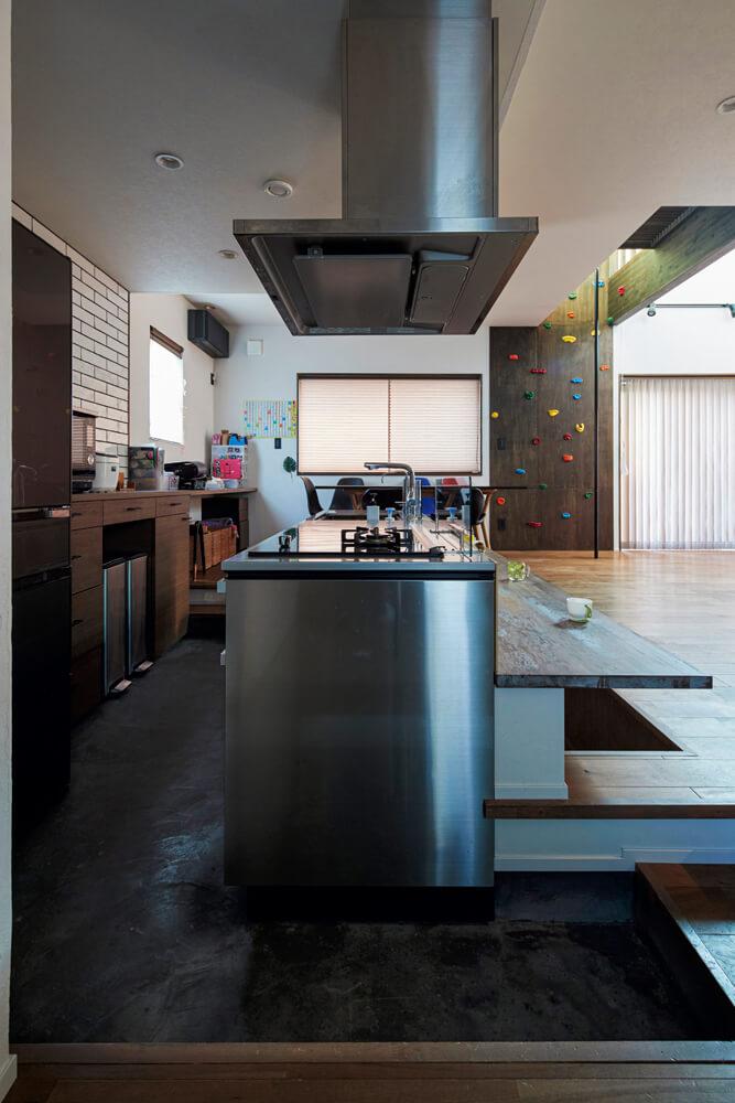 目線合わせのために床レベルを一段下げたキッチンは、IHとガスのハイブリッド型。モールテックスを採用した床には床暖房が入っていて冬でも暖か