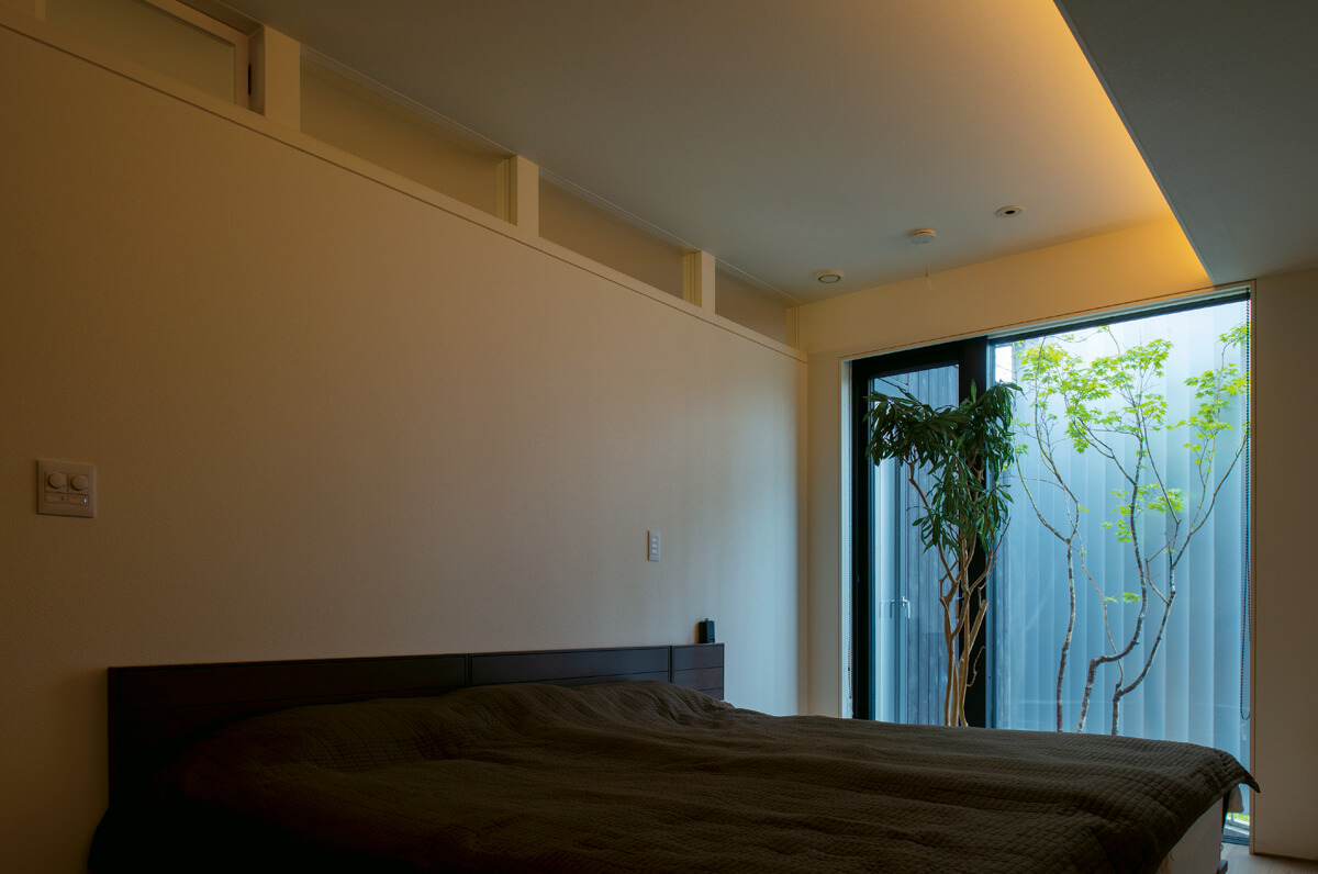 DKに隣接する主寝室。間仕切り壁と天井の間には、光と空気の通り道となる開口が設けられている。北側の坪庭も窓越しに楽しめる