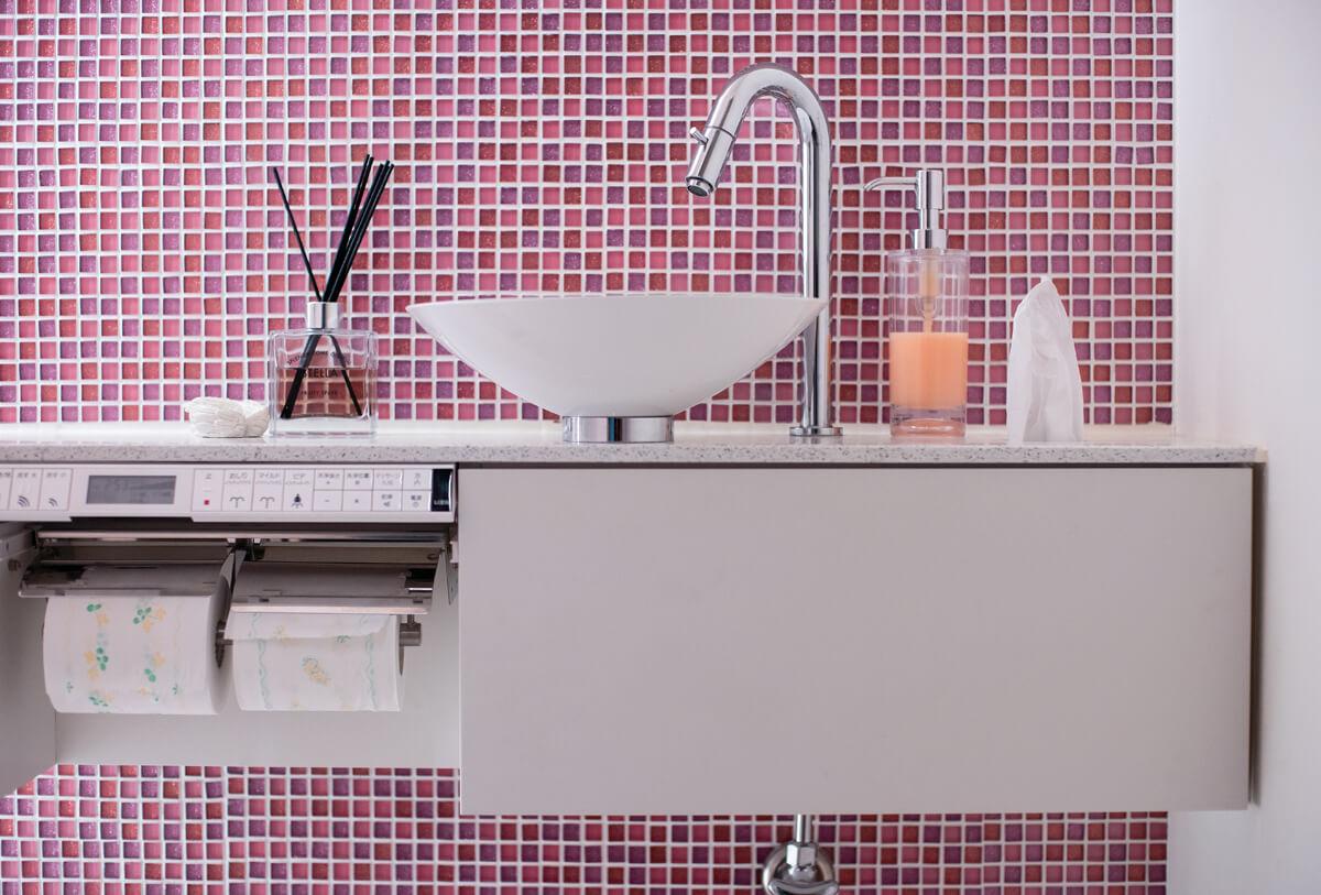 黒とグレーを基調に整えられた室内で、トイレだけはラメ入りのガラスタイルを用い、明るく華やかな印象に仕上げた