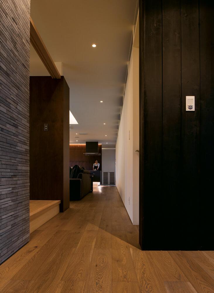 玄関ホールからLDK側を見る。間仕切りの壁や造作収納は同じ高さで統一することで、端正で開放感のある空間を実現