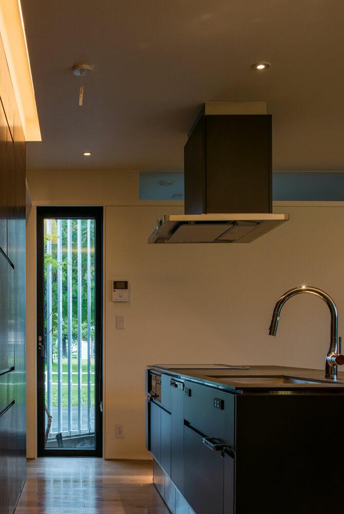 セラミック天板を採用したアイランドキッチンは、名古屋さんデザインの造作。坪庭を望む窓は、採光と換気を兼ねる