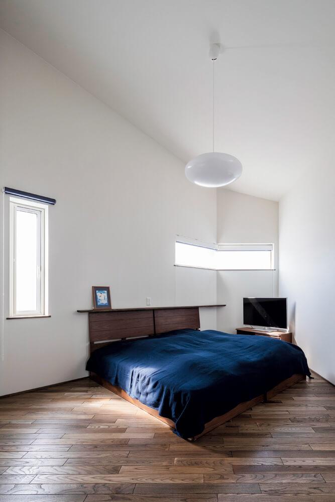 約9帖の寝室。変形敷地の影響で一部鋭角になっている角には、テレビを置いて有効活用している