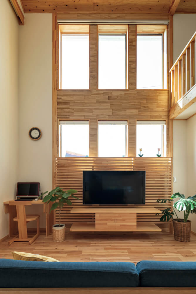 リビングの高い3連窓が明るい空間を実現。窓枠と一体型のテレビ台は床面から少し浮かせ、パソコンコーナーも設えた