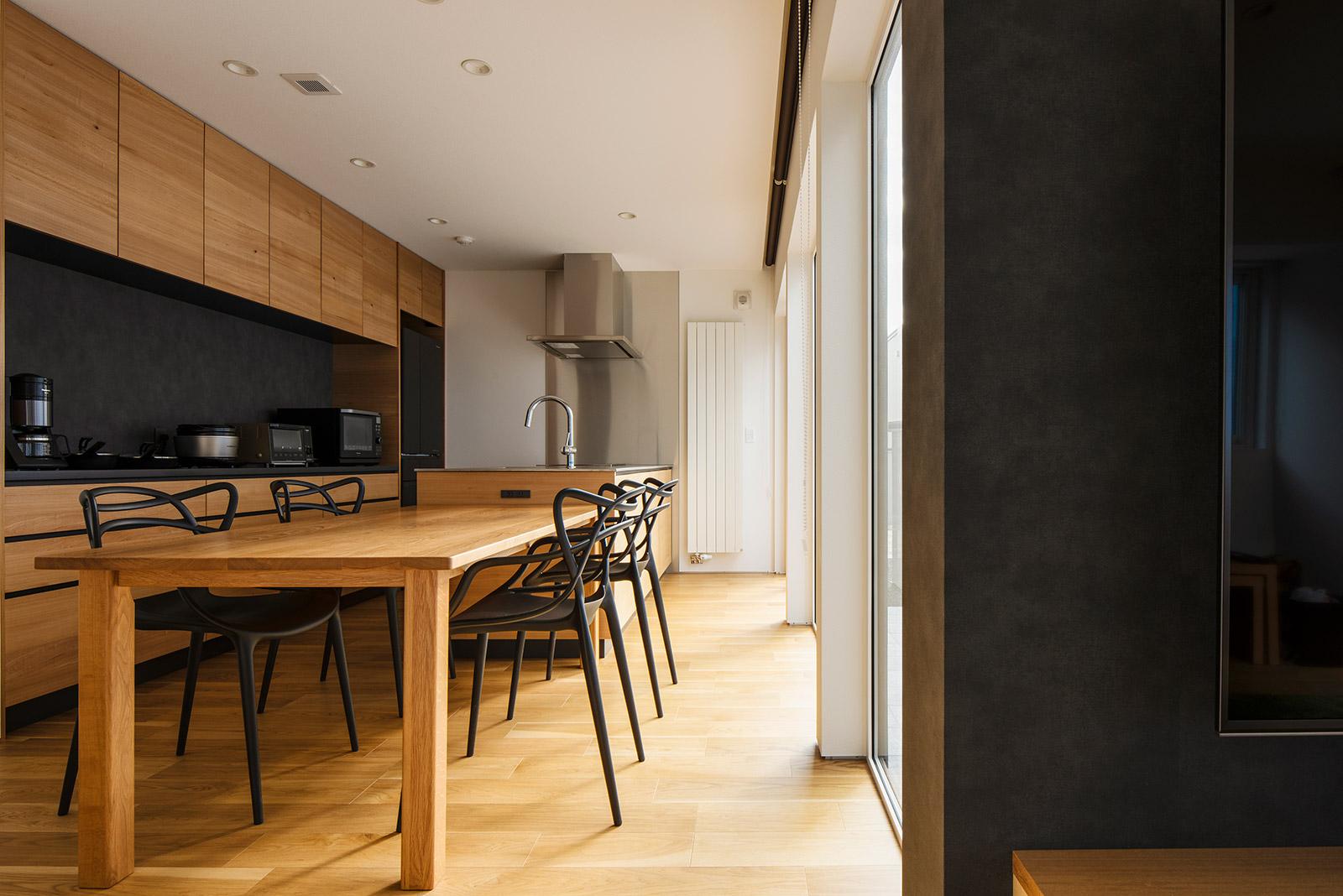 中庭を一望できる明るいダイニング・キッチンは、ご夫妻のお気に入り。大開口で中庭とつながることで、空間に心地よい広がりが生まれた。造作キッチンには、ニレの面材とステンレス、黒のアクセントウォールを採用。家事動線に合わせた収納プランが、美しさと使い勝手の良さを両立させている