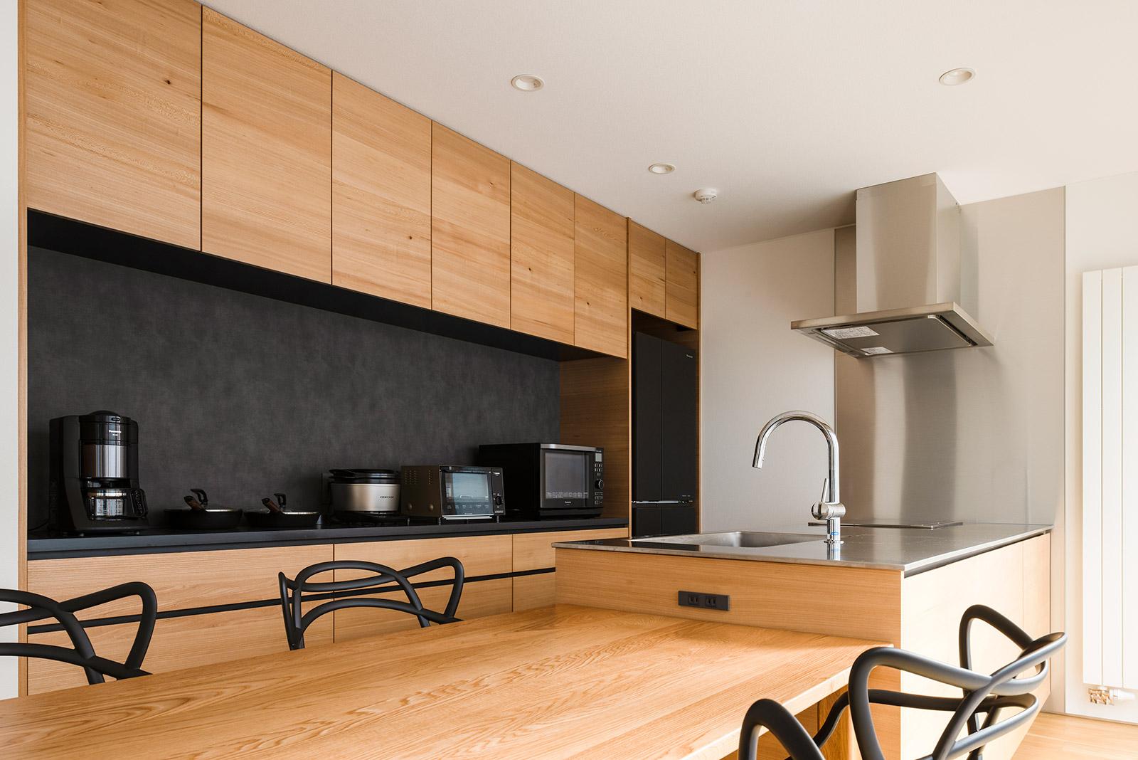 造作キッチンには、ニレの面材とステンレス、黒のアクセントウォールを採用。家事動線に合わせた収納プランが、美しさと使い勝手の良さを両立させている