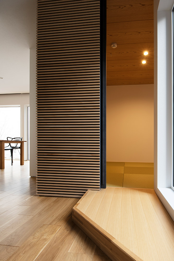 玄関ホールに隣接して、Hさんが希望していた和室をレイアウト。木のボーダーとクロス巻きの造作建具、琉球畳を用いて、和モダンな空間に仕上げた