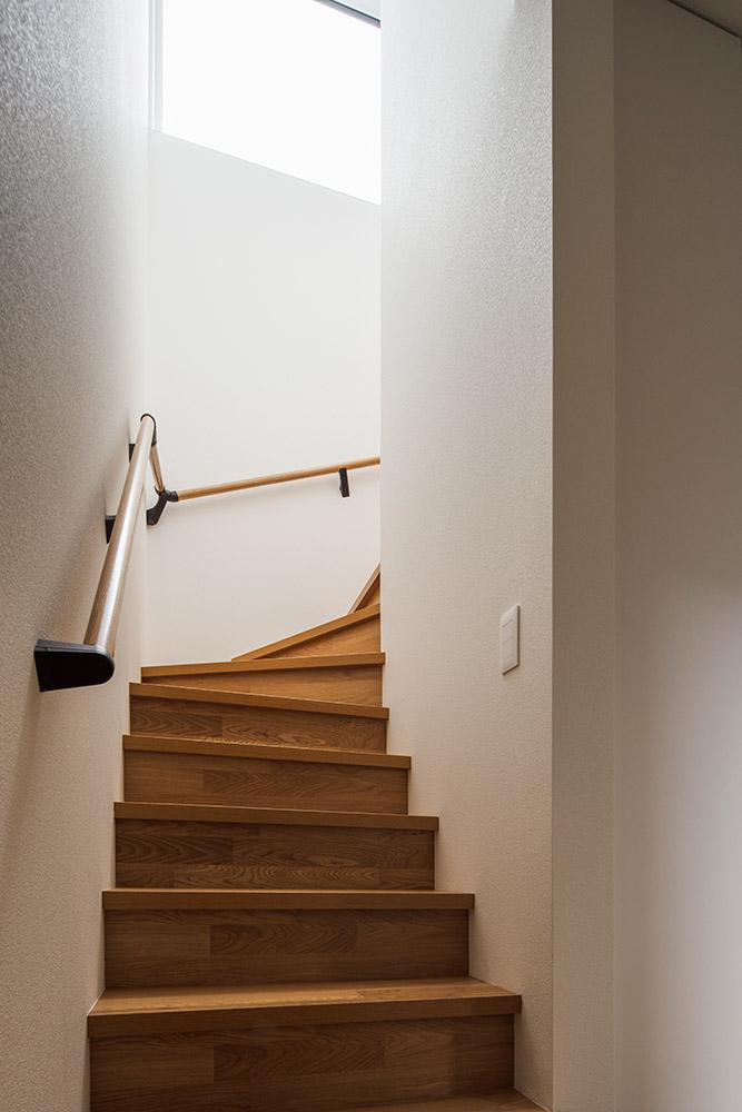2階へつながる階段にも採光窓を設け、明るさを確保。窓からこぼれる自然光が白壁にやわらかな陰影を描く