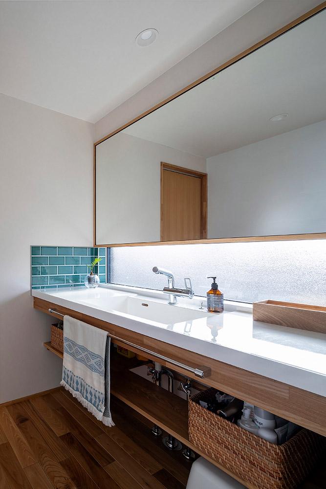 玄関からすぐアクセスできる広い洗面台はタイルがアクセント